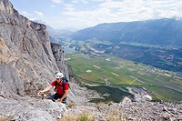 Climber on the Che Guevara via ferrata on Monte Casale in the Sarca Valley, Lake Garda region, with Toblino lake at back, Trentino, Italy, Europe