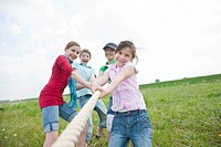Four friends, three girls and a boy playing tug of war in a meadow