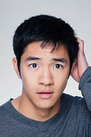 Studio portrait of young man scratching head