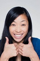 Studio portrait of young woman showing thumbs up sign