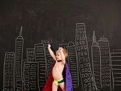 Cute toddler boy 2_3 standing against blackboard with city skyline drawn on it