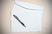 Two white envelopes with pen on desk