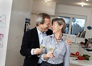Mature couple drinking champagne in kitchen