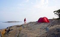 Woman camping on rock by sea