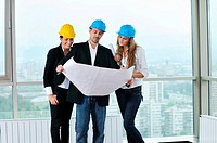 young arhitect group in big bright modern new apartment looking blueprints and building plans