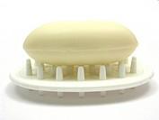 Beige Seife auf Seifenablage vor weißem Hintergrund