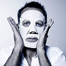 studio portrait of a man using facial mask beauty treatmen