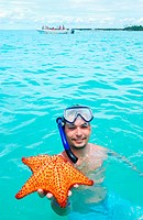 Snorkel man holding red starfish