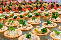 many tartlets with meat salad under mayonnaise and parsley on buffet table, shallow DOF