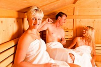 Three people one male, two female enjoying a hot sauna, having a casual chat