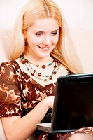 Young charming fair_haired woman works on portable computer.