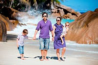 Young beautiful family of four walking along tropical beach