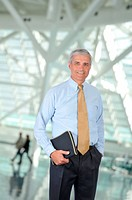 Standing Businessman notebook and hand in pocket in Building Lobby with blurred people in the background