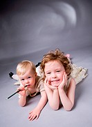 Studio photo of two sisters over gray background