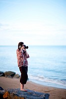 Beautiful young female photographer taking pictures on beach