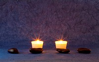 A set of massage stones on blue/purple wallpaper with candles