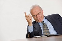 Senior executive pointing with his finger during a meeting.