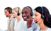 Attractive man and his team working in a call center against a white background