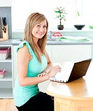 Delighted blond woman using her laptop smiling at the camera at home in the kitchen