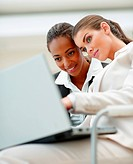 Two young business women working together on a laptop