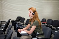 Young woman listens in audience through earphones