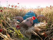 Beautiful blonde lady laying in poppy field
