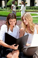 Two attractive you businesswomen or female executives meeting outside with laptop computer and folder