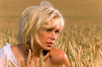 beautiful blonde sitting on a field of wheat