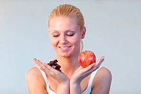 Beautiful woman holding chocolate and apple trying to decide which one to eat with focus on woman