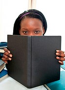 Cute afro_american teenager behind a book looking at the camera against white background