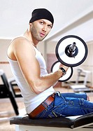 man makes exercises with bar in exercise room