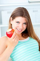 Positive woman eating an apple smiling at the camera
