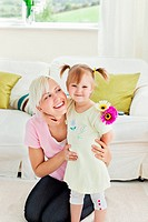 Blond woman getting surprised by her daughter in living room