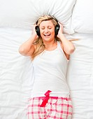 Top view of a woman in pyjamas listening music with headphones lying on her bed