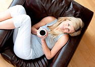 Top view of a woman relaxing on an armchair with coffee in the living_room