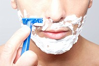 man shaving with razor