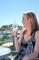 young woman with glass of wine in outdoors cafe or restaurant