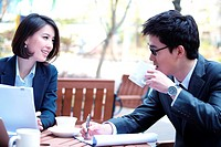 Businesswoman And Businessman Working At Outdoor Café