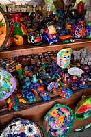 Many colorful souvineers for sale at a mexican souvineer stand all aranged neatly on a shelf.