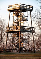 A huge fire watch tower or ranger station overlooks hundreds of acres of forest.