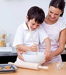 Adorable little boy preparing cookies with her mother in the kitchen