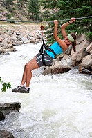 An attractice and atletic girl makes tyrolean traverse over a rushing river