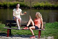 Young women, 25-30 years, eating on a bench after exercise