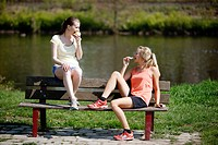 Young women, 25_30 years, eating on a bench after exercise