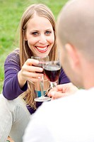 Young romantic couple celebrating with wine in picnic