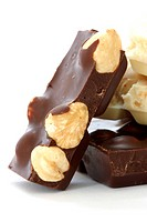 Dark and white chocolate with whole hazelnuts close up on white background