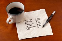 working on household budget _ napkin concept with coffee cup on wooden table