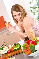 Cooking _ smiling woman with glass of white wine and vegetable in modern kitchen