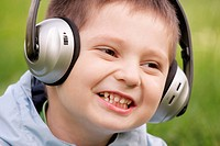 Closeup portrait of smiling little boy in headphones looking sideways