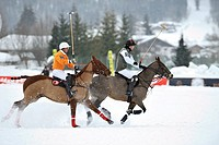 Two polo players galloping through the snow, Tarquin Southwell of team Hawker Beechkraft followed by Francisco Podesta of team Kitzbuehel, polo played...